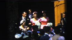 1961: group of well-dressed individuals emerge smiling from behind wooden door Stock Footage