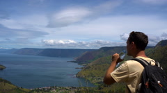 Male traveler drinking water and looking at Toba lake in North Sumatra Indonesia Stock Footage