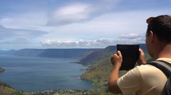 Male traveler taking photo on tablet of Toba lake in North Sumatra, Indonesia Stock Footage
