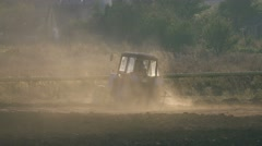Farm tractor plowing the land, leaving behind a cloud of dust at sunset Stock Footage