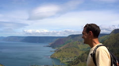 Young man pointing at Toba Lake, North Sumatra, Indonesia Stock Footage