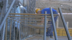 Construction worker binding reinforcement, bars in focus close up by Sheyno. Stock Footage