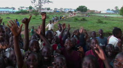 Medium shot of a crowd of children at a refugee camp Uganda, Africa, waving at Stock Footage