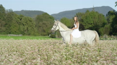 SLOW MOTION: Beautiful innocent girl riding white horse in pink flowering field Stock Footage