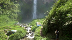 Young man backpacker walking towards beautiful Sipiso-Piso waterfall Stock Footage