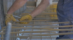 Worker tying reinforcement bars with pliers and wire by Sheyno. Stock Footage
