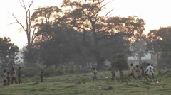 Pan-left shot of villagers walking along a path in Uganda, Africa. Stock Footage