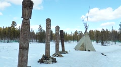 Sami idols standing in the woods on a spring day, next to them tent. Stock Footage