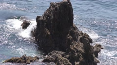 Waves crashing on rock in the ocean surging blue water over jagged enscarpmen Stock Footage