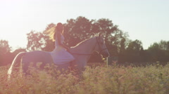SLOW MOTION: Smiling girl in white dress riding horse in blooming pink field Stock Footage