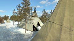 Several of the Sami tents stand in the winter woods. Stock Footage