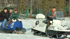 People ride on a snow banana hitched to a snowmobile. Stock Footage