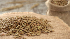 Close-up of lentil rotating on burlap. Rustic wooden background. Seamless Stock Footage
