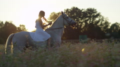 CLOSE UP: Girl in white dress riding horse in flowering pink field at sunrise Stock Footage