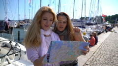 Two young traveler guided by a paper map on the city's waterfront. Slow Motion. Stock Footage