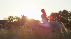CLOSE UP: Pretty girl riding horse without reins in blooming field at sunrise Stock Footage