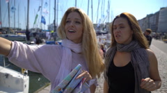 Two young traveler guided by a paper map on the city's waterfront. Stock Footage