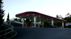 Petro-Canada gas station at sunset with car leaving in front of camera. Stock Footage