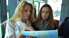 Two young traveler riding the tram in an unfamiliar city and use a paper map. Stock Footage