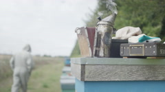 4K Bee keeper walking away from his hives, focus on equipment in foreground Stock Footage