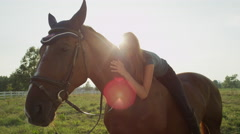 CLOSE UP: Cute young Caucasian brunette girl laying on horse and petting him Stock Footage