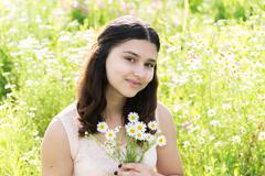 Girl teenager with bouquet of daisies on summer meadow Stock Photos