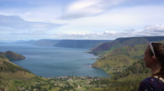 Female traveler looking at Toba lake in North Sumatra, Indonesia Stock Footage