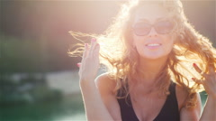 Sexy young woman smiling at the camera, flirting. The sun is shining in her hair Stock Footage