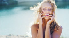 Young woman smiling into the camera, playing with her beautiful hair. On the Stock Footage