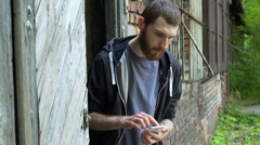 Skinny man using smartphone while standing next to the abandoned building, stead Stock Footage