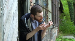 Man burn joint while standing next to the abandoned building, steadycam shot Stock Footage