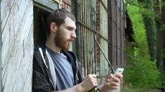 Man drinking wine and using smartphone while standing next to the abandoned buil Stock Footage