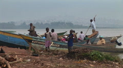 Boys standing before fishing boats at Gaba village, along the shores of Lake Stock Footage