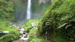 Young woman backpacker walking towards beautiful Sipiso-Piso waterfall Stock Footage