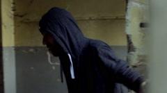 Man walking in abandoned, dark building and wearing hood, steadycam shot Stock Footage