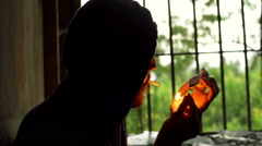Man sitting in the darkness and smoking cigarette, steadycam shot Stock Footage