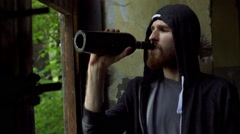 Sad man standing in the abandoned building and drinking alcohol, steadycam shot Stock Footage