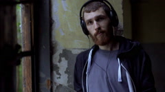 Man listening music and looking morose while standing in the abandoned building, Stock Footage
