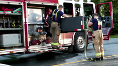 Coquitlam firefighters wrap up their water hoses on fire truck in rescue scene. Stock Footage