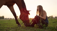 CLOSE UP: Young cheerful girl hanging out with horse grazing on pasture field Stock Footage