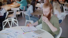 Ginger man working in cafe and drink coffee on table graph and papper. Behind Stock Footage