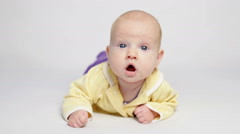 Cute baby in yellow shirt lying on the belly Stock Footage