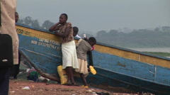 Medium-shot of a woman and children leaning against a boat on the shores of Lake Stock Footage