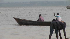 Medium-shot of a man rowing a john-boat amidst a group of other fishers on Lake Stock Footage