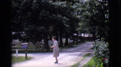 1968: a woman in a dress, walking across a dirt road towards a car as she waves Stock Footage