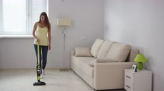 Girl with wireless vacuum cleaner Stock Footage