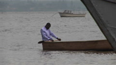 Pan-right of a the oarsman of a fishing boat on Lake Victoria, Uganda. Stock Footage