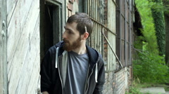 Man standing next to the abandoned building and smoking joint Stock Footage