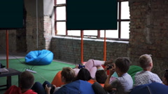 Children playing video games while sitting in bean bag chairs, childhood Stock Footage