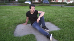 A teen-age boy sitting on the edge of a life size maze and thinking Stock Footage